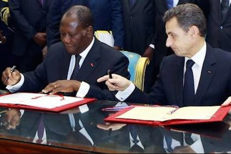 Alassane Ouattara et Nicolas Sarkozy signant des contrats.